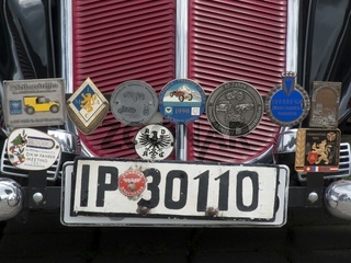Diverse Plaketten und historisches Kennzeichen an einem Oldtimer