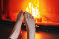 close up of girl's feet in front of fireplace