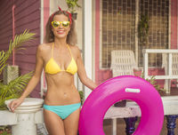 Pretty young happy woman wearing bikini and sunglasses posing with pink inflatable ring isolated on the background of pink house
