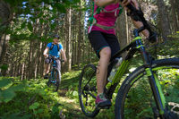 Active sporty couple riding mountain bikes on forest trail .