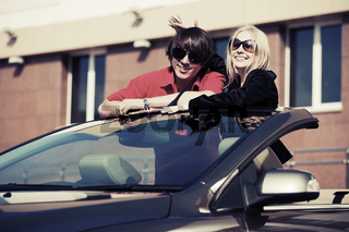 Happy young couple at the convertible car