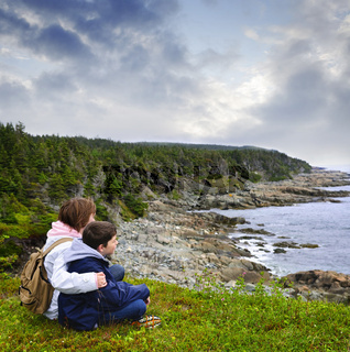 Children sitting at Atlantic coast in Newfoundland