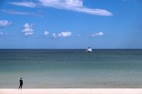 A lonely woman at the beach and a single ship on the Baltic Sea