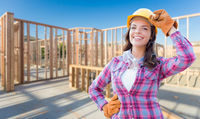 Young Attractive Female Construction Worker Wearing Gloves, Hard Hat and Protective Goggles At Construction Site