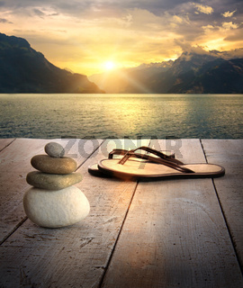 View of sandals and rocks on dock at sunset