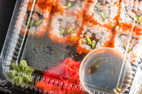 Sushi rolls, ginger and soy in plastic container top view
