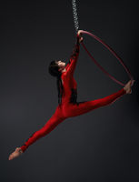 Young pretty gymnast with red hoop studio portrait