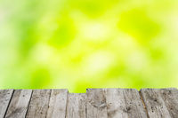 Wooden table over green sunny background