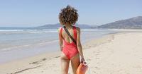 Female lifeguard goes along beach