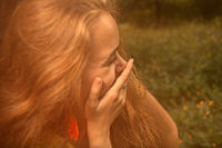 Blond haired girl hiding her smile by hand and looking away
