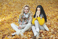 Women in autumn park drink coffee
