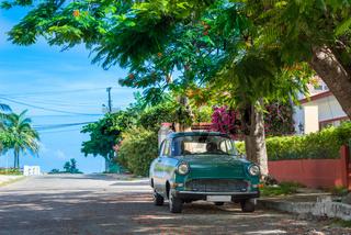 HDR - Grüner amerikanischer Oldtimer parkt unter einem Baum in der Seitenstrasse in Varadero Kuba