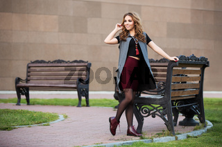 Happy young fashion woman with long curly hairs walking on city street