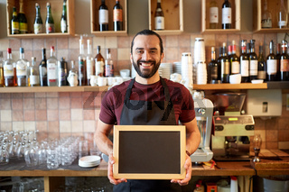 happy man or waiter with chalkboard banner at bar