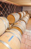 Wine Barrels and Bottles Age Inside Cellar