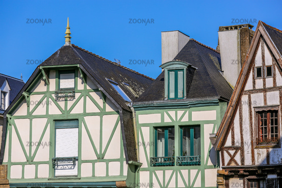 This is a close up view of a white Tudor style cottage in Brittany, France with green and brown exterior timbers.