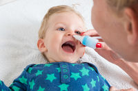 mom cleans baby's nose with blower