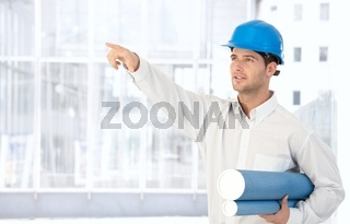 Architect in hardhat pointing