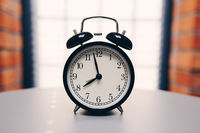 Retro alarm clock on table on white background