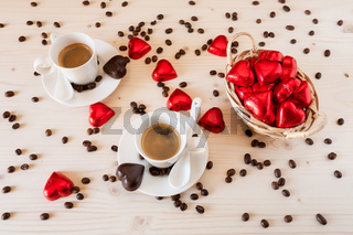 Red chocolate hearts in a small basket and two cups of coffee