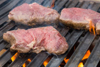 Raw beef steaks on grill with flames.