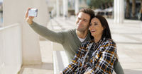 Happy laughing couple taking their selfie