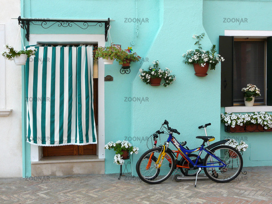 turquoise house wall with bikes and flowers