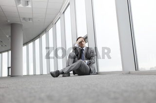 Businessman sitting on floor