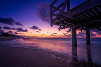 Sunset over wooden pier on the sea beach