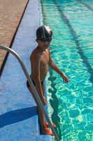 Cute boy ready to dive in the sport swimming poolb standing on border near pool ladder