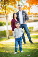 Outdoor Portrait of Happy Mixed Race Chinese and Caucasian Parents and Child.