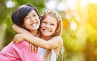Asiatisches und kaukasisches Mädchen umarmen sich