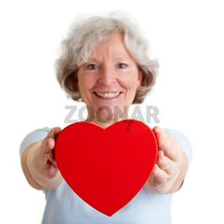 Seniorin schenkt rotes Herz