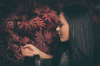 sensual woman face in front of red leaves in the side profile