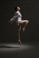 Slim girl wearing only shirt dancing in the dark