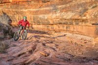 riding fat bike on slickrock at  canyon bottom