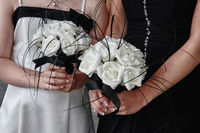 Two bridesmaids holding a bouquet of white flowers. Black and white wedding.