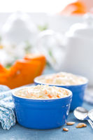 Cooking on kitchen table delicious mini casserole with cottage cheese and pumpkin for breakfast. White background