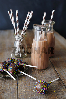 Bottles of chocolate milk and cake pops on plate