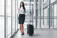 Successful confident young business woman with coffee and suitcase in an office setting
