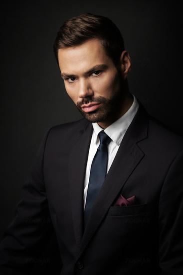 Handsome young businessman portrait on black background