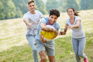 Freunde im Park spielen mit einem Ball