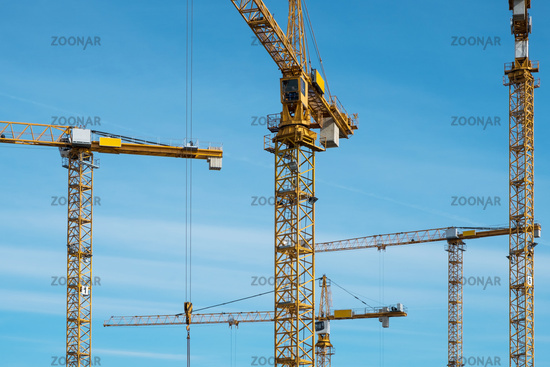 cranes on blue sky at construction site