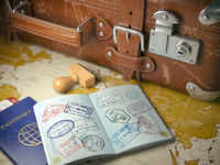 Travel or turism concept.  Old  suitcase  with opened passport with visa stamps.