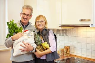 Senioren mit Einkaufstasche in Küche