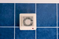 Air conditioner fan on blue tiled wall indoors