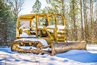 bulldozer at construction site covered with snow