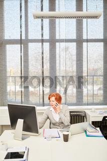 Seniorin mit Smartphone am Computer