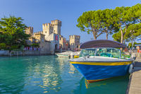 Motorboat at port Sirmione in front of castello Scaligero at lake Garda, Brescia, Lombardy, Italy