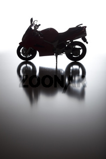 Silhouette of Street Motorcycle on Reflective Surface